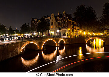 Amsterdam night canal - Stripes of light of a tourboat...
