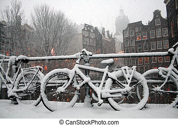 Amsterdam Winter Scene - A bicycle stands under heavy...