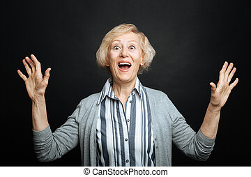 Amused aging woman expressing emotions in the studio -...