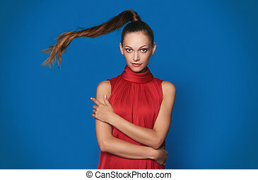 Amused beautiful young woman in red dress