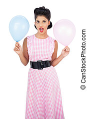 Amused black hair model holding balloons on white background