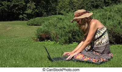 Amused blonde woman with hat working with her notebook sitting on lawn in sunny park. 4K