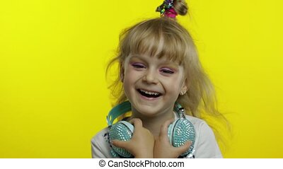 Amused stylish child laughing out loud with tears, feeling carefree joyful after hearing funny joke, silly anecdote. Little fun blonde kid teen girl 5 years old with headphones on yellow background
