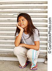 Amused homeless child - Homeless poor girl sitting on the...
