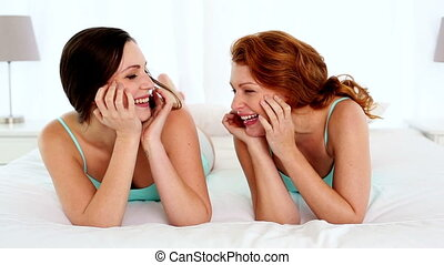 Amused laughing women lying on bed in bright bedroom