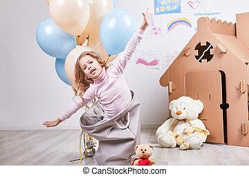 Amused little girl fantasizes about flying