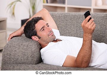 Amused man lying on the sofa sending a text message