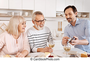 Amused mature man enjoying family weekend at home
