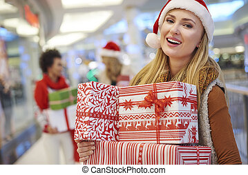 Amused woman with a pile of Christmas presents