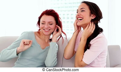 Amused women listening to music