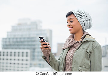 Amused young model in winter clothes looking at her mobile phone outside on a cloudy day