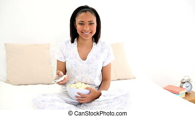 Amused young woman eating popcorn