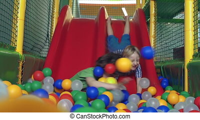 Amusement Park - Close up of two kids sliding from the...