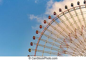 Amusement park giant wheel against blue sky background