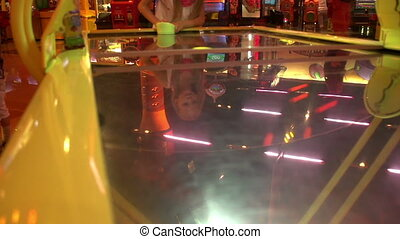 Girl playing Air hockey table for in the amusement park