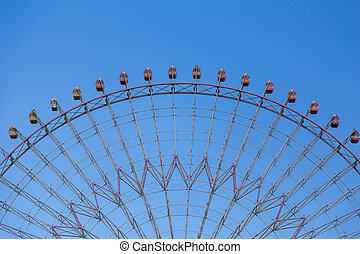 Amusement part of giant wheel with clear blue sky background