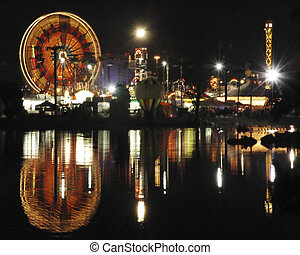 A nighttime image of an amusement park with its reflections in a pond.
