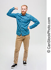 Amusing bearded man showing his muscles