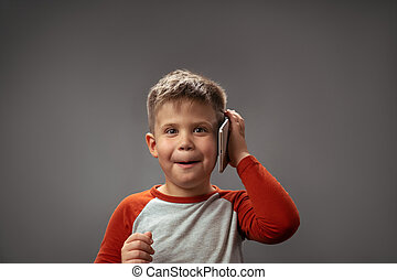 Amusing boy holds mobile phone or tablet by his ear in the studio. Portrait of a boy with a gadget. Isolated on gray background. High quality photo