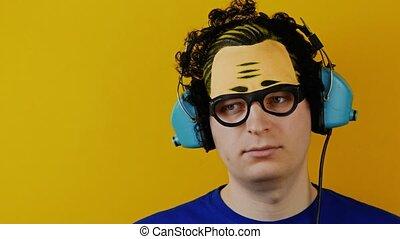 amusing curly man listening to music in a retro headphones...