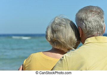 Amusing elderly couple having rest on beach