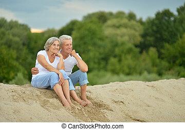 Amusing elderly couple on the beach