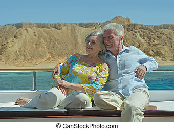 Amusing elderly couple have a ride in a boat on sea