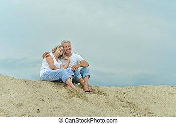 Amusing elderly couple went to the beach to enjoy the sea breeze