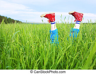 Amusing feet cheerfully sticking out of a grass