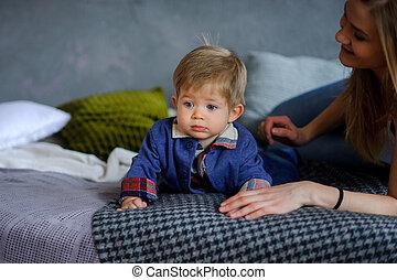 Amusing little boy lies on a big bed.