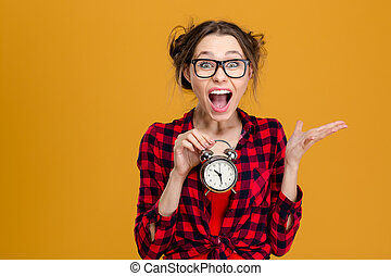 Amusing pretty young woman holding alarm clock and shouting...
