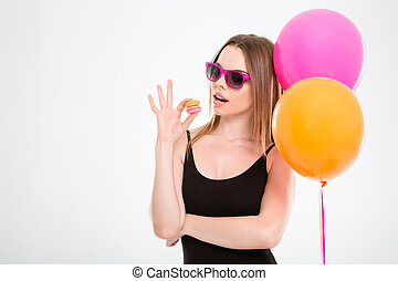 Amusing young woman in pink sunglasses eating macaroons -...