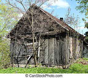 An abandoned broken wooden house with boarded-up windows in a forgotten village
