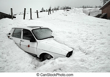 An abandoned car covered in snow