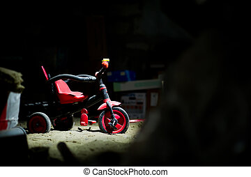 an abandoned children's bike dusting in the attic among the old trash. The concept of forgotten childhood, loneliness. Copy space