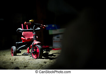 an abandoned red children's tricycle stands under a layer of dust in the basement among a variety of junk. The concept of forgotten childhood, loneliness