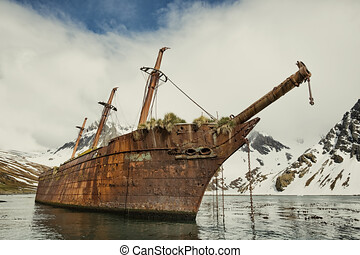 An abandoned ship in Antarctica, abandoned ship at the north pole with ice mountains in the background