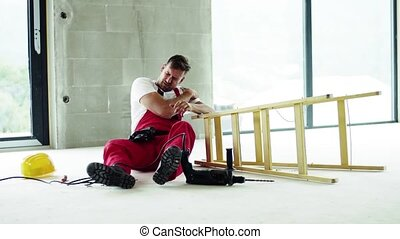 An accident of a man worker at the construction site, holding an injured shoulder.