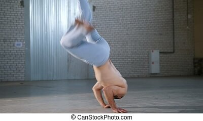 An acrobatic shirtless man training his skills. Showing...