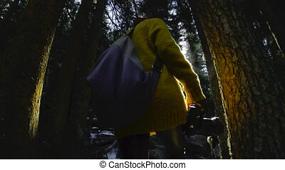 An active healthy hipster girl-photographer with a camera in her hands walks through the forest. Rear view of a walking girl walking through the forest. The girl comes and photographs Low key 60 FPS slow motion.