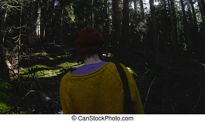 An active healthy hipster girl-photographer with a camera in her hands walks through the forest. Low key 60 FPS slow motion.