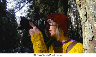 An active healthy hipster girl-photographer with a camera in her hands walks through the forest. The girl is taking pictures. Low key 60 FPS slow motion.