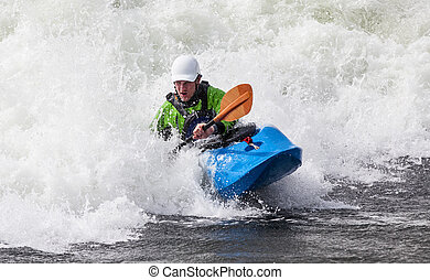 kayaker - an active male kayaker rolling and surfing in...