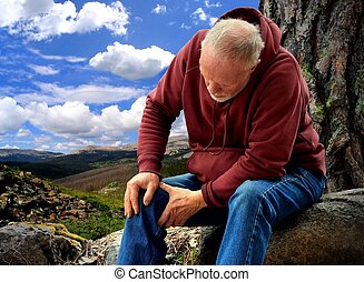 An active senior with joint pain - A hiker resting along a...