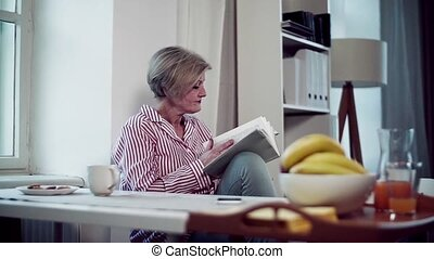 An active senior woman sitting at the table at home, reading...