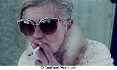 An active senior woman standing outdoors in town, smoking a...