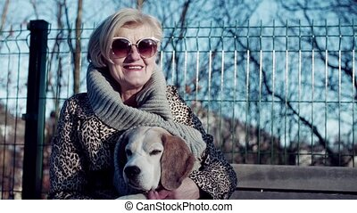 An active senior woman with a dog sitting on a bench in town in winter.
