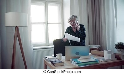 An active senior woman with laptop and smartphone working in home office.