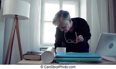 An active senior woman with laptop working in home office,...