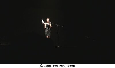 an actress in a black dress reads a monologue, standing on stage in the light of a spotlight.